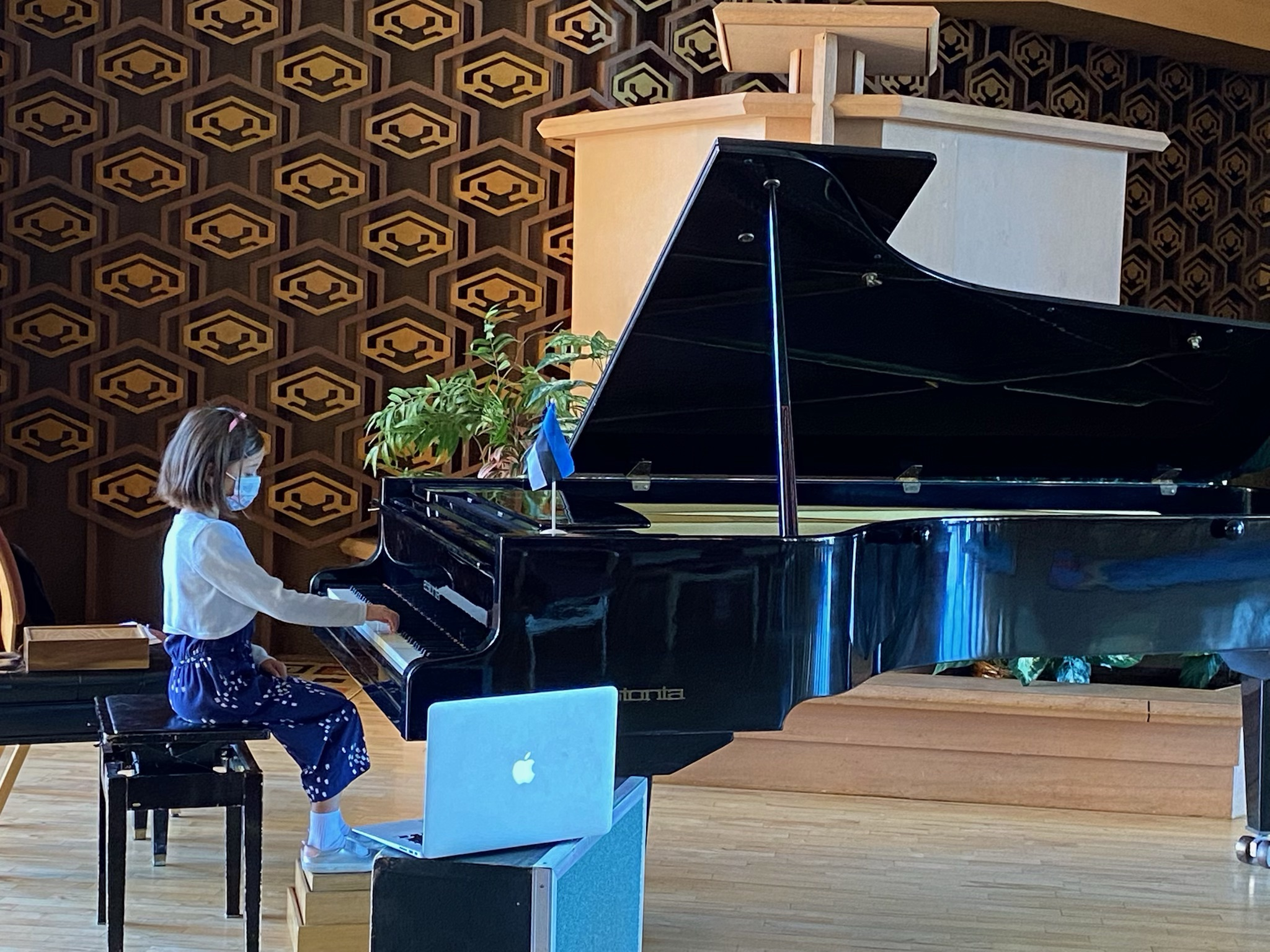 A student plays the grand piano in the Peace United Church sanctuary